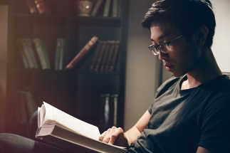 Attractive peaceful young man in glasses sitting and reading book at home